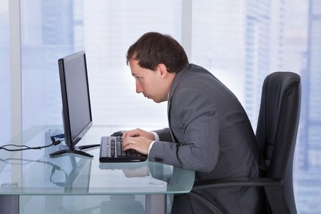 Hunched shoulders and forward head positioning due to poor desk posture.