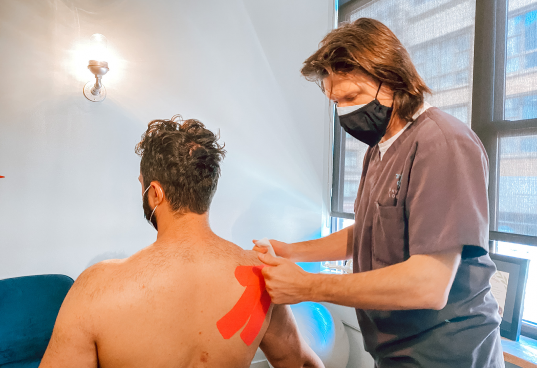 Dr. Stephen Szaro, DC, Chiropractor in Brooklyn, NY demonstrates how to apply Kinesio tape on shoulder of a patient at Physio Logic NYC.